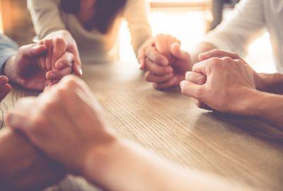 Fyra personer sitter vid ett bord och håller varandras händer