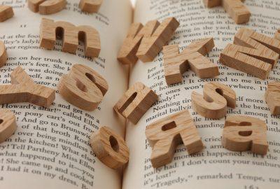 Öppen bok med olika träbokstäver ovanpå